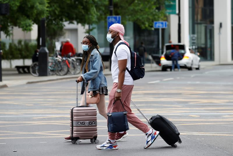 People wear protective masks as they walk with suitcases through the city centre, amid the outbreak of the coronavirus disease (COVID-19) in Manchester