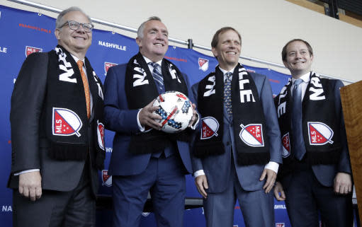 Ian Ayre, second from left, poses for pictures after being introduced as the first chief executive officer of the Nashville MLS franchise Monday, May 21, 2018, in Nashville, Tenn. Ayre is a former CEO of the Liverpool Football Club of the English Premier League. From left are Nashville Mayor David Briley, Ayre, lead owner John Ingram, and emcee Will Alexander. (AP Photo/Mark Humphrey)