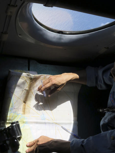 A Vietnamese Air Force crew member looks at a map on board a flying aircraft during a mission to search for the missing Malaysia Airlines flight MH370 in the Gulf of Thailand over the location where Chinese satellite images showed possible debris from the missing Malaysian jetliner, Thursday, March 13, 2014. (AP Photo)