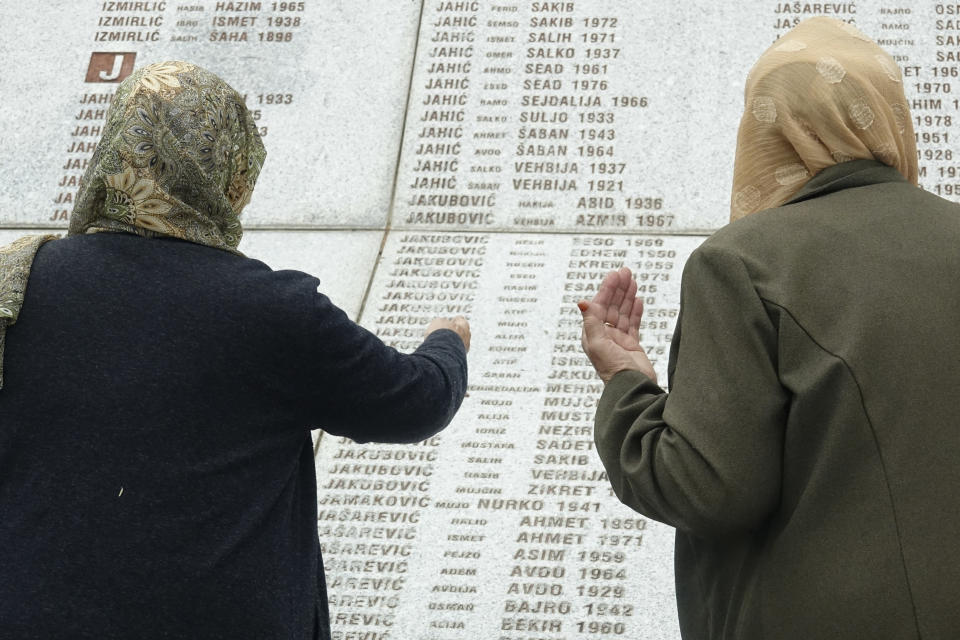 Women who lost their relatives in Srebrenica massacre looks at names at the memorial cemetery in Potocari near Srebrenica, Bosnia, Friday, May 28, 2021. U.N. judges on Tuesday, June 8 deliver their final ruling on the conviction of former Bosnian Serb army chief Radko Mladic on charges of genocide, war crimes and crimes against humanity during Bosnia's 1992-95 ethnic carnage. Nearly three decades after the end of Europe's worst conflict since World War II that killed more than 100,000 people, a U.N. court is set to close the case of the Bosnian War's most notorious figure. (AP Photo/Eldar Emric)