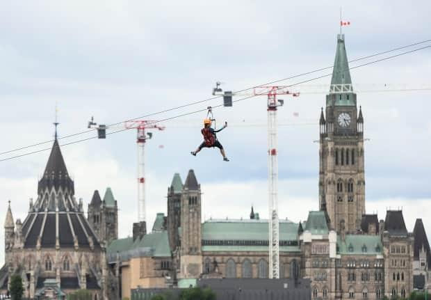 A person uses their phone to record themselves as they ride a zip line connecting Ottawa and Gatineau, Que., last month. (Justin Tang/The Canadian Press - image credit)