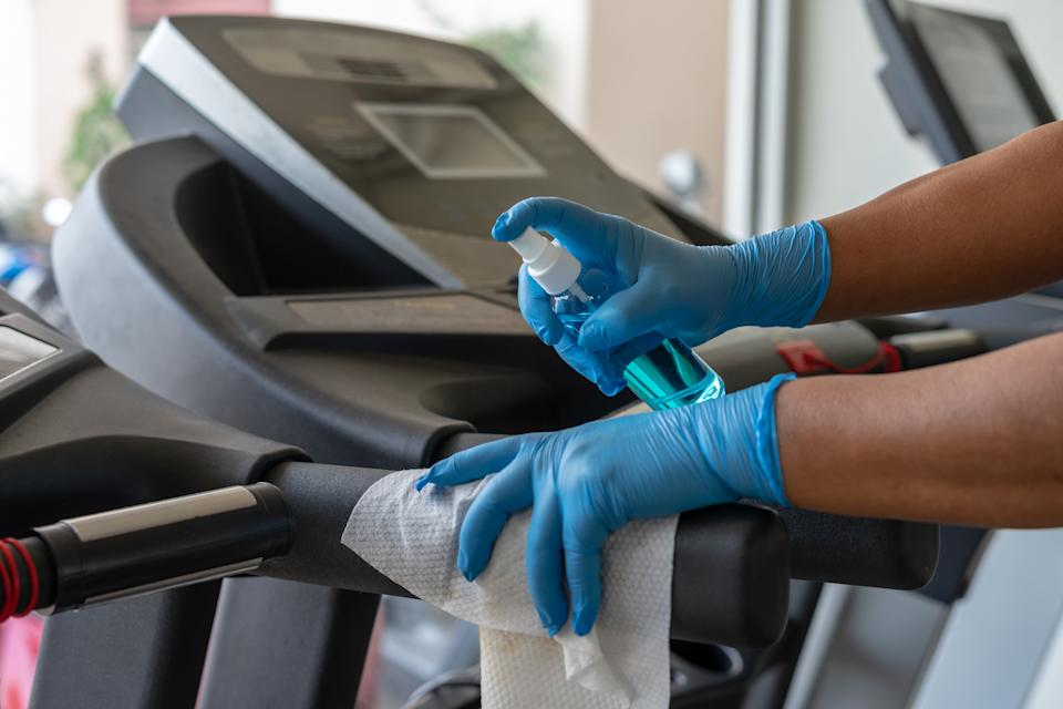 Staff using wet wipe and a blue sanitizer from the bottle to clean treadmill in gym. Antiseptic,disinfection ,cleanliness and healthcare, Anti Corona virus (COVID-19).
