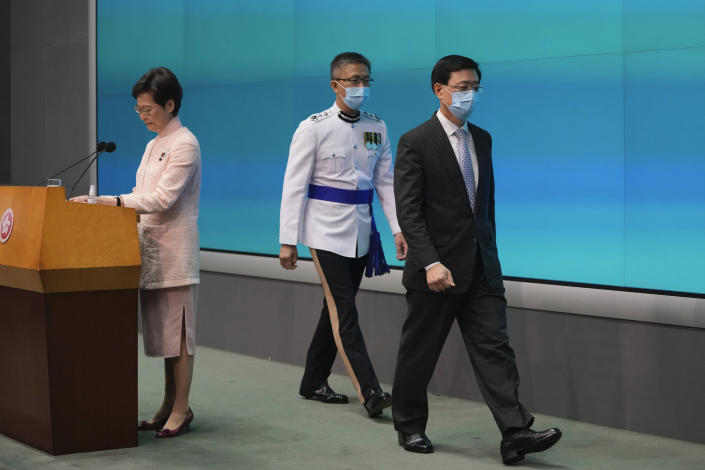 Hong Kong's Chief Executive Carrie Lam, left, speaks as Chief Secretary John Lee, right, and Commissioner of Police Raymond Siu leave a news conference in Hong Kong, Friday, June 25, 2021. China on Friday promoted Hong Kong's top security official to the territory's No. 2 spot as Beijing continues to clamp down on free speech and political opposition. (AP Photo/Kin Cheung)