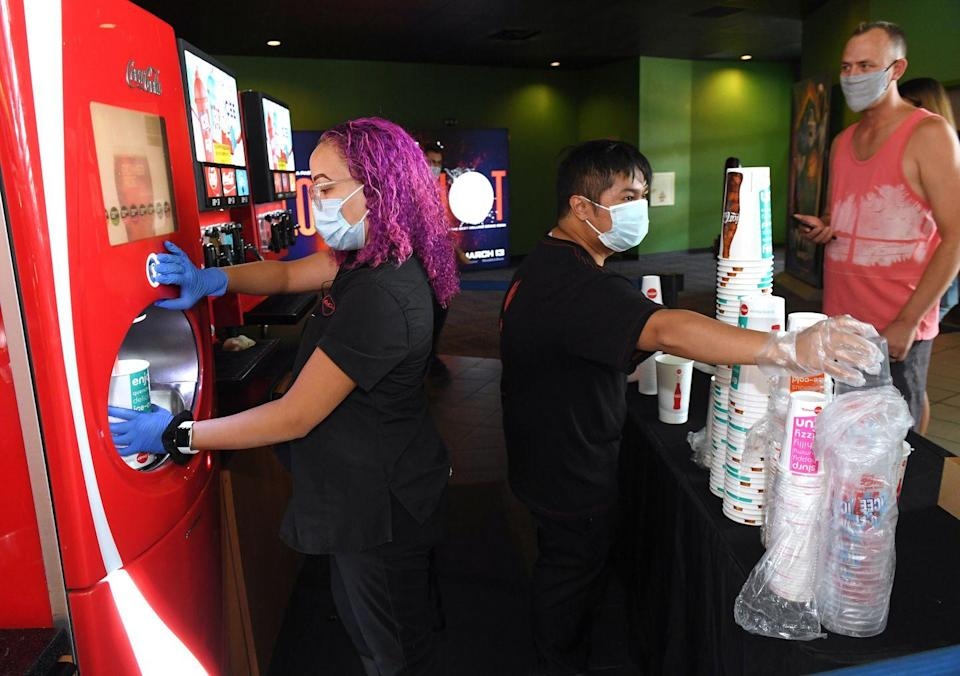 <p>Supervisor Patrics Davis (L) and Tyler Salazar get drinks for customers at AMC Town Square 18 on August 20 in Las Vegas, Nevada.</p>