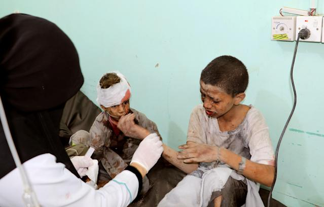 <p>A doctor treats children injured by an airstrike in Saada, Yemen, Aug. 9, 2018. (Photo: Naif Rahma/Reuters) </p>