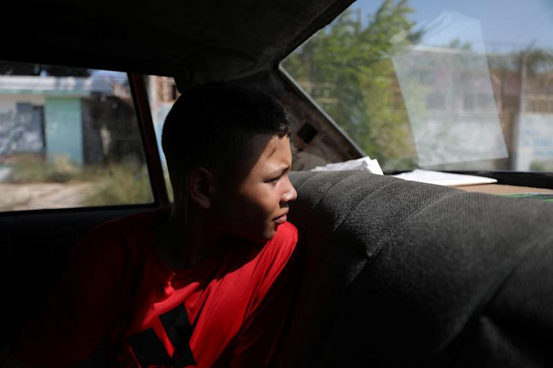 Baseball little league player Ibrahim Ruiz, 13, sits in his father's car as they drive to fill fuel in Maracaibo, Venezuela. (Photo: Manaure Quintero/Reuters)