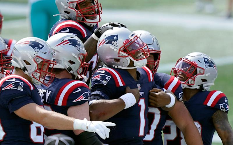 New England Patriots quarterback Cam Newton (1) celebrates his rushing touchdown against the Miami Dolphins with teammates in the first half of an NFL football game, Sunday, Sept. 13, 2020, in Foxborough, Mass. - AP
