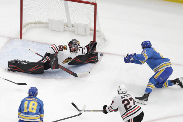 St. Louis Blues' Tyler Bozak, right, scores past Chicago Blackhawks goaltender Corey Crawford during the third period of an NHL hockey game Saturday, Dec. 14, 2019, in St. Louis. The Blues won 4-3. (AP Photo/Jeff Roberson)