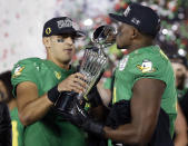 Oregon quarterback Marcus Mariota, left, and linebacker Tony Washington celebrate with the trophy after their win against Florida State during the second half of the Rose Bowl NCAA college football playoff semifinal, Thursday, Jan. 1, 2015, in Pasadena, Calif. (AP Photo/Lenny Ignelzi)