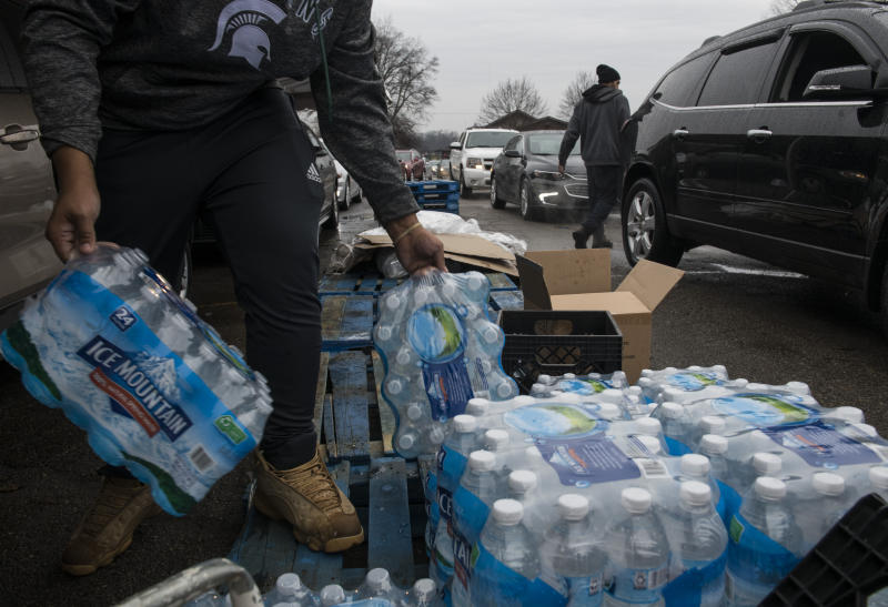 FLINT, MICHIGAN - DECEMBER 20: Workers load bottled water into vehicles waiting in line at a water distribution site at Greater Holy Temple in Flint, Mich., on Thursday, December 20, 2018. (Photo by Brittany Greeson/The Washington Post via Getty Images)
