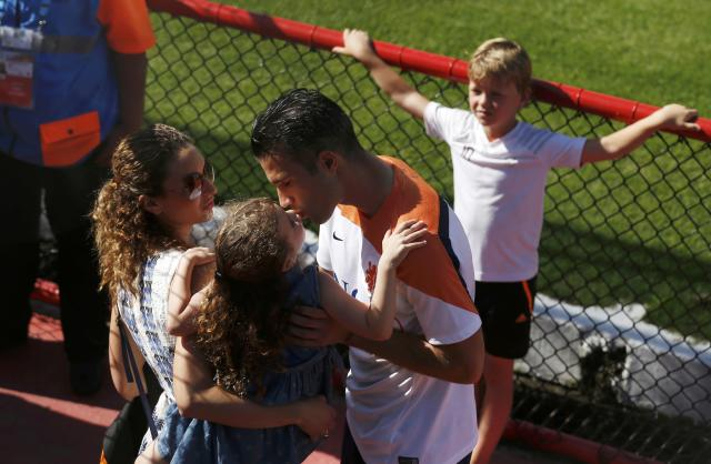 Netherlands' national soccer player Robin van Persie kisses his daughter as his wife holds her after a training session for the 2014 World Cup in Rio de Janeiro, June 14, 2014. REUTERS/Pilar Olivares (BRAZIL - Tags: SOCCER SPORT WORLD CUP)