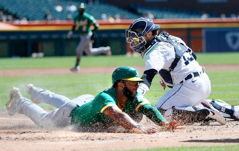 Oakland Athletics' Elvis Andrus beats the tag from Detroit Tigers catcher Eric Haase (13) to score from first base on a double by Starling Marte during the second inning of a baseball game Thursday, Sept. 2, 2021, in Detroit.