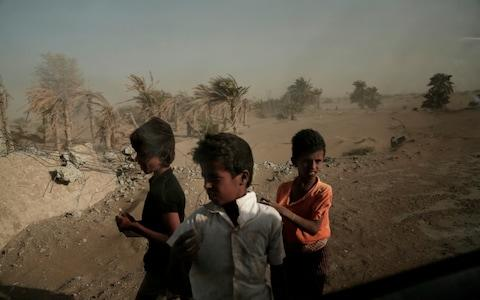 <span>Homeless children stand on the road from Khoukha to Taiz in Yemen</span> <span>Credit: AP </span>