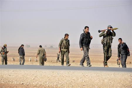 Members of the Kurdish People's Protection Units carry their weapons as they walk in the west of the city of Ras al-Ain