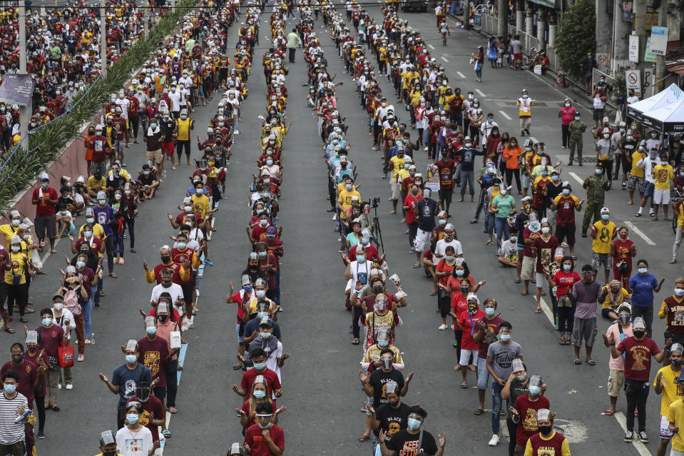 Thousands of Catholic devotees line up as they celebrate the feast day of the Black Nazarene at the Minor Basilica of the Black Nazarene in downtown Manila, Philippines, Saturday Jan. 9, 2021. Hundreds of church workers and police were spread around the area to maintain order and enforce strict social distancing health protocols. The annual procession has been cancelled amid the threat of the ongoing COVID-19 pandemic in one of Asia's biggest religious events. (AP Photo/Gerard Carreon)