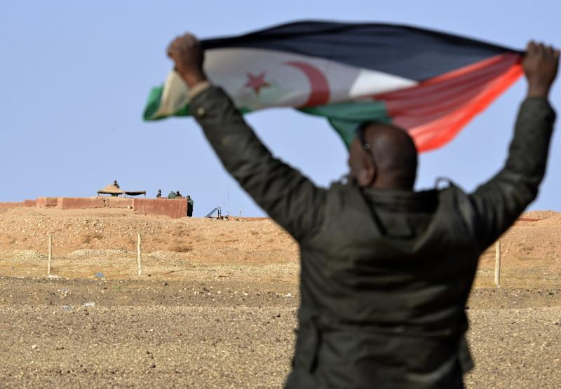 A Saharawi man holds up a Polisario Front flag in the Al-Mahbes area near Moroccan soldiers guarding the wall separating the Polisario controlled Western Sahara from Morocco on February 3, 2017
