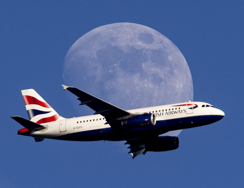 The moon rises as a British Airways aircraft flies on its way to the airport in Frankfurt, Germany, Thursday, June 13, 2019. (AP Photo/Michael Probst)