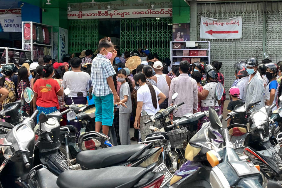 People wait outside a shop where face masks and vitamins are being given away in Mandalay, Myanmar, Thursday, July 8, 2021. Myanmar is facing a a rapid rise in COVID-19 patients and a shortage of oxygen supplies just as the country is consumed by a bitter and violent political struggle since the military seized power in February. (AP Photo)