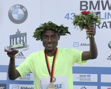 Winner Kenenisa Bekele of Ethiopia celebrates during the victory ceremony at the Berlin marathon in Berlin, Germany, September 25, 2016. REUTERS/Fabrizio Bensch