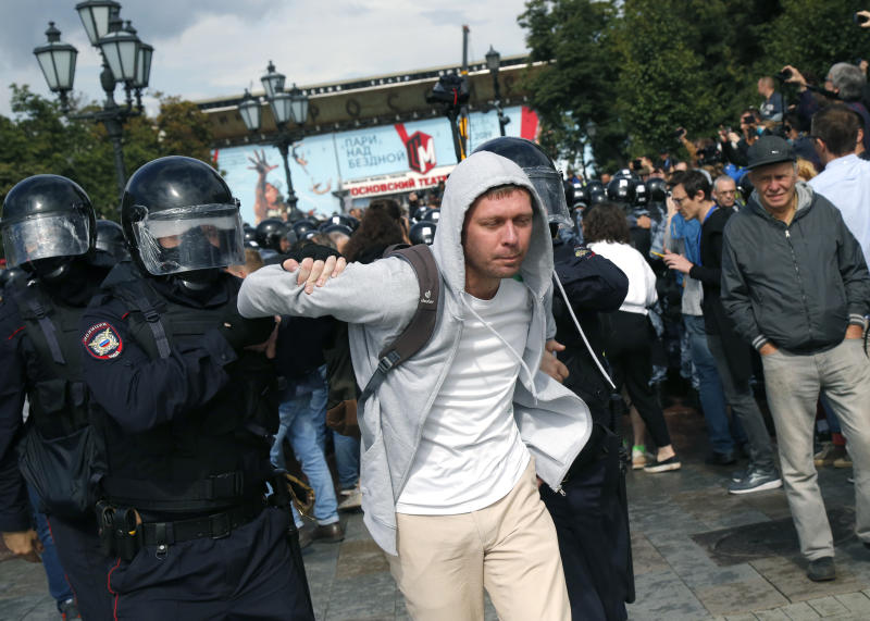 Police officers detain a protestor, during an unsanctioned rally in the center of Moscow, Russia, Saturday, Aug. 3, 2019. Moscow police on Saturday detained nearly 90 people protesting the exclusion of some independent and opposition candidates from the city council ballot, a monitoring group said, a week after arresting nearly 1,400 at a similar protest. (AP Photo/Alexander Zemlianichenko)