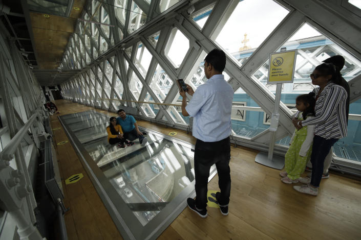 Visitors pose for photographs on the glass walkway at the Tower Bridge Visitor Attraction, in London, on the first day it was allowed to reopen as the British government relaxes its third coronavirus lockdown restrictions, Monday, May 17, 2021. (AP Photo/Matt Dunham)