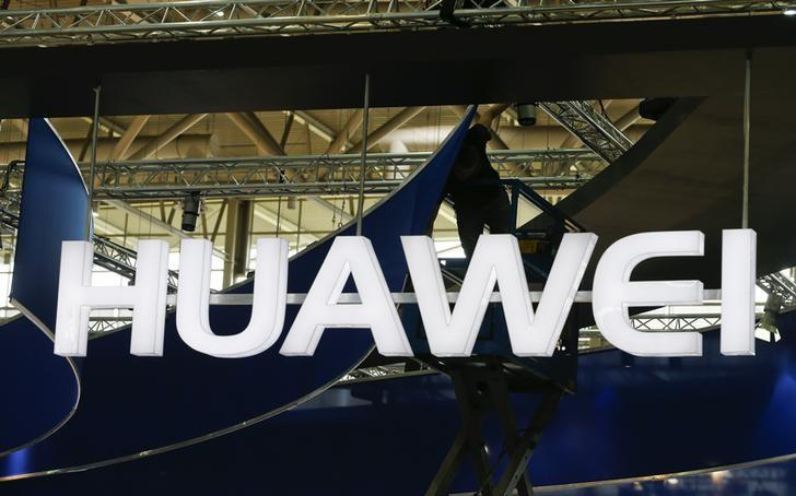 A worker adjusts the logo at the stand of Huawei at the CeBIT trade fair in Hanover