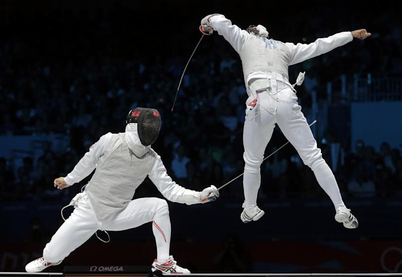 Ryo Miyake of Japan competes against Andrea Baldini of Italy, right, compete in the gold medal match during the men's foil team fencing competition at the 2012 Summer Olympics, Sunday, Aug. 5, 2012, in London. (AP Photo/Dmitry Lovetsky)