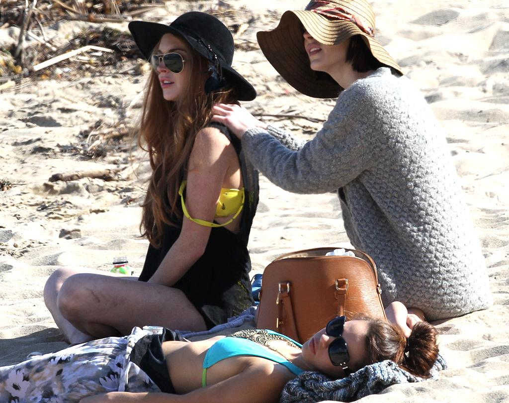 """<p class=""""MsoNormal"""">With her formal probation behind her — buh-bye, morgue duty! —Lindsay Lohan has had more free time on her hands and she's been spending it with her sister, Ali. The sisters, both wearing floppy hats, kicked back at a Malibu beach, where the star had her little sister give her a back massage. (4/10/2012)</p>"""