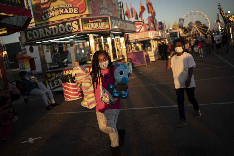A girl wears a face mask while walking through the Mississippi State Fair, Wednesday, Oct. 7, 2020, in Jackson, Miss. At the fair, which is held every year in October and attracts people from across the racial spectrum, the vast majority of Black people are wearing masks. Most white people do not. (AP Photo/Wong Maye-E)