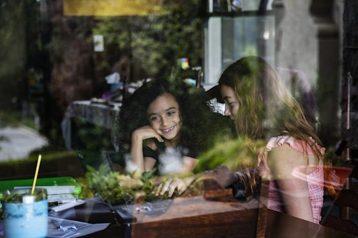 "Allison Furbush, left, and Ellie Bristow are seen through a front porch window while teaming up on a science project. <span class=""copyright"">(Gina Ferazzi / Los Angeles Times)</span>"