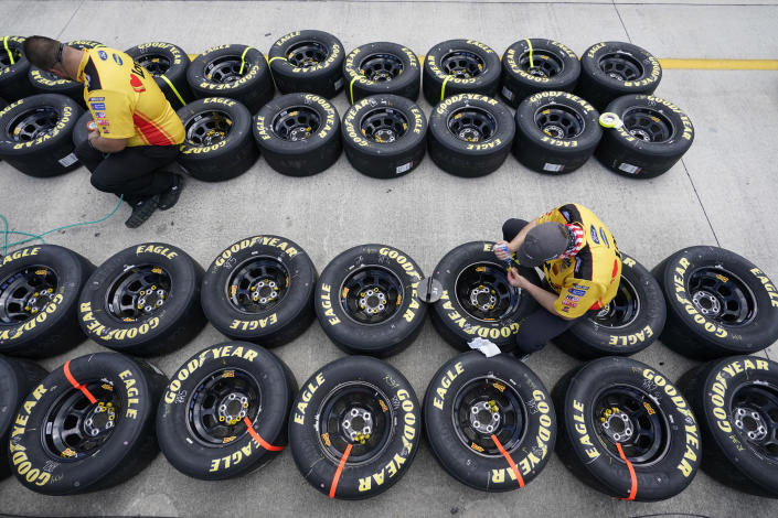 Crew members for Michael McDowell (34) work on tires before the start of a NASCAR Cup Series auto race, Sunday, Feb. 28, 2021, in Homestead, Fla. (AP Photo/Wilfredo Lee)