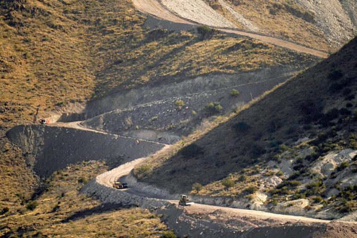 "FILE - A pathway cleared by explosives to make way for border wall construction separates Mexico, right, and the United States, Wednesday, Dec. 9, 2020, in Guadalupe Canyon, Ariz. President Biden on Wednesday ordered a ""pause"" on all wall construction within a week, one of 17 executive edicts issued on his first day in office, including six dealing with immigration. The order leaves projects across the border unfinished and under contract after Trump worked feverishly last year to reach 450 miles, a goal he announced was achieved eight days before leaving office. (AP Photo/Matt York)"