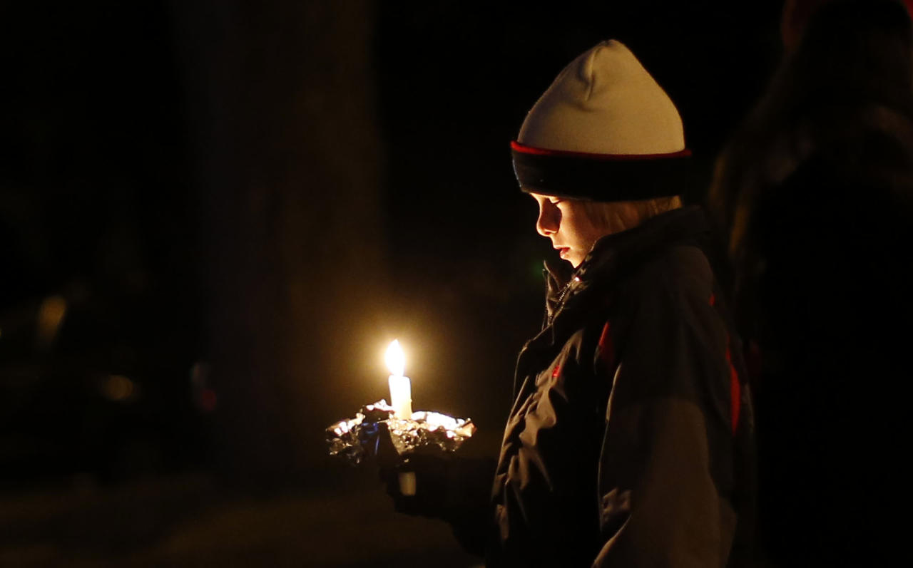 A mourner attends a candlelight vigil at Ram's Pasture to remember shooting victims, Saturday, Dec. 15, 2012, in Newtown, Conn. A gunman walked into Sandy Hook Elementary School in Newtown on Friday and opened fire, killing 26 people, including 20 children. (AP Photo/Jason DeCrow)