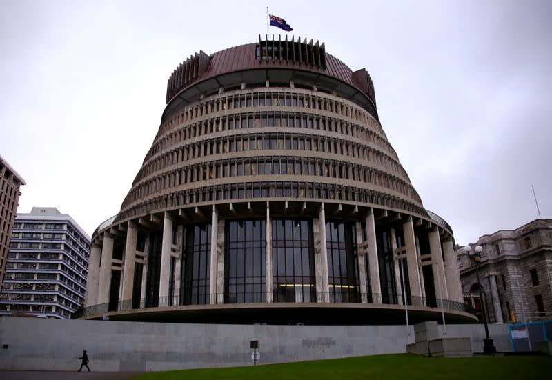 FILE PHOTO: A pedestrian walks past the New Zealand parliament building known as the Beehive in central Wellington, New Zealand
