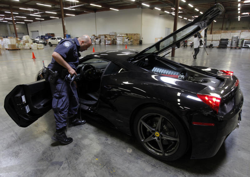 """U.S. Customs and Border Protection (CBP) officer Paulo Zanetti holds a fiber optic camera used to check the interior of gas tanks, next to a 2010 Ferrari 458 Italia """"supercar,"""" one of 20 high-end stolen vehicles that were intercepted on their way to Honk Kong and Vietnam, in Carson, Calif., on Tuesday, April 3, 2012. (AP Photo/Damian Dovarganes)"""