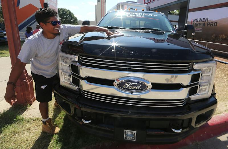 In this Monday, Oct. 9, 2017, photo, David Ruiz polishes a fully-loaded F-450 Super Duty Limited, the biggest version of the Ford F-Series, on display at the State Fair of Texas in Dallas. Buyers are increasingly outfitting their pickups with all the comforts of luxury cars, from heated and cooled seats to backup cameras to panoramic glass roofs. (AP Photo/LM Otero)