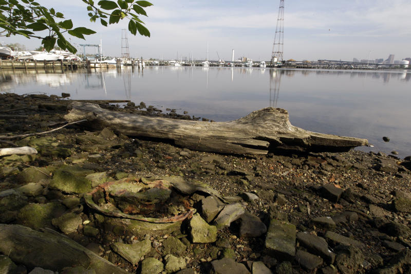 """This photo taken April 16, 2012, shows remnants of a tire and rim along the shoreline of the Middle Branch of the Patapsco River in Baltimore, Md. This archival image was taken for the """"Documerica"""" program, begun in 1972 by the new Environmental Protection Agency, to document subjects of environmental concern. (AP Photo/Patrick Semansky)"""