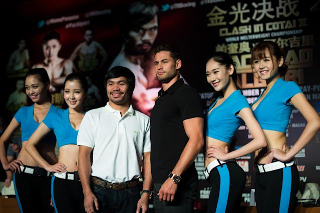 Philippine boxing icon Manny Pacquiao (3rd L) and Chris Algieri (3rd R) of the US pose with ring girls during a pre-fight press conference in Shanghai, on August 26, 2014 (AFP Photo/Johannes Eisele)