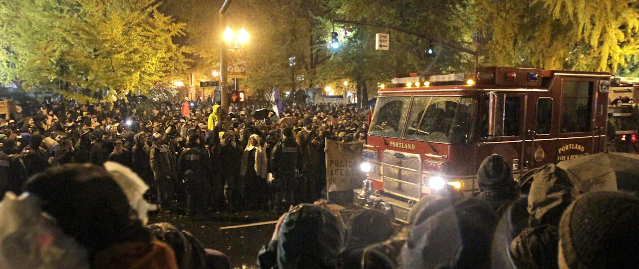 A fire truck moves through thousands of protesters in the streets as the deadline nears when the city wants them to vacate the Occupy Portland Camp in Portland, Ore., Sunday, Nov. 13, 2011. Mounted police and police in riot gear moved in but were forced to back down by the crowd. (AP Photo/Don Ryan)