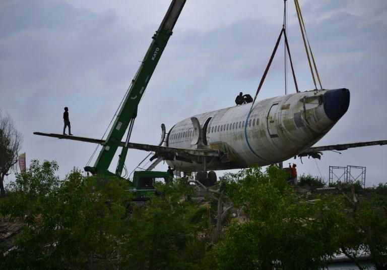 It took a week to transport the plane's parts to the cliff, its new owner said (AFP/SONNY TUMBELAKA)