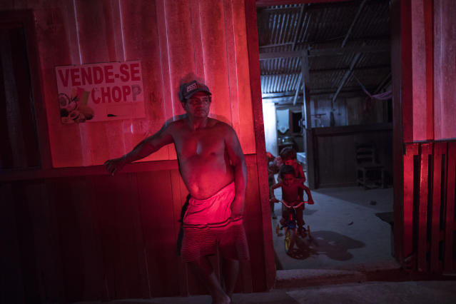 In this Sept. 2, 2019 photo, a small shop owner, who sells a little bit of everything, is illuminated by brake lights while standing outside his home in the Cajueiro village, Para state, Brazil. Brazil's 900,000 indigenous people make up about 0.5% of the country's population and their reservations account for about 14% of its territory. (AP Photo/Rodrigo Abd)