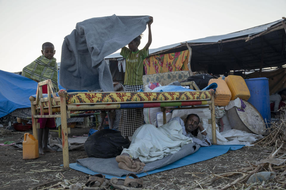 Tigray refugees who fled the conflict in the Ethiopia's Tigray wake up at Hamdeyat Transition Center near the Sudan-Ethiopia border, eastern Sudan, Thursday, Dec. 3, 2020. Ethiopian forces on Thursday blocked people from the country's embattled Tigray region from crossing into Sudan at the busiest crossing point for refugees, Sudanese forces said.(AP Photo/Nariman El-Mofty)