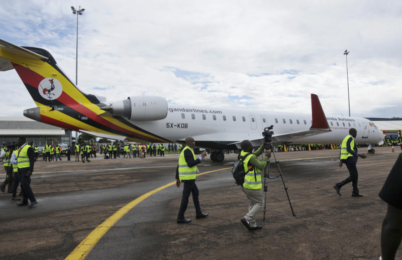 FILE - In this Tuesday, April 23, 2019 file photo, cameramen film at a ceremony to mark the arrival of two CRJ-900 jets from Canadian aerospace company Bombardier for Uganda's national carrier Uganda Airlines, at the airport in Entebbe, Uganda. Questions are swirling in Africa and elsewhere over the financial wisdom of sustaining prestige carriers that have a tiny share of an aviation market that sees no recovery in sight as sub-Saharan Africa faces its first recession in a quarter-century amid coronavirus-related travel restrictions. (AP Photo/Ronald Kabuubi, File)