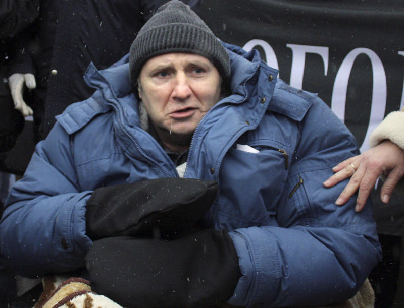RETRANSMISSION OF MOSB110 FILE  In this Sunday, Nov. 21, 2010 file photo, Russian journalist Mikhail Beketov who has extensively covered the Khimki forest dispute and was brutally beaten in 2008, is seen during a rally on Pushkin Square to support journalists and activists and demand full investigation into their beatings in central Moscow,  Russia. Mikhail Beketov, a Russian journalist who lost a leg and was left brain-damaged after a brutal assault that followed his campaigns against a highway project outside Moscow, has died on Monday, April 8, 2013. He was 55. (AP Photo/Mikhail Metzel, file)