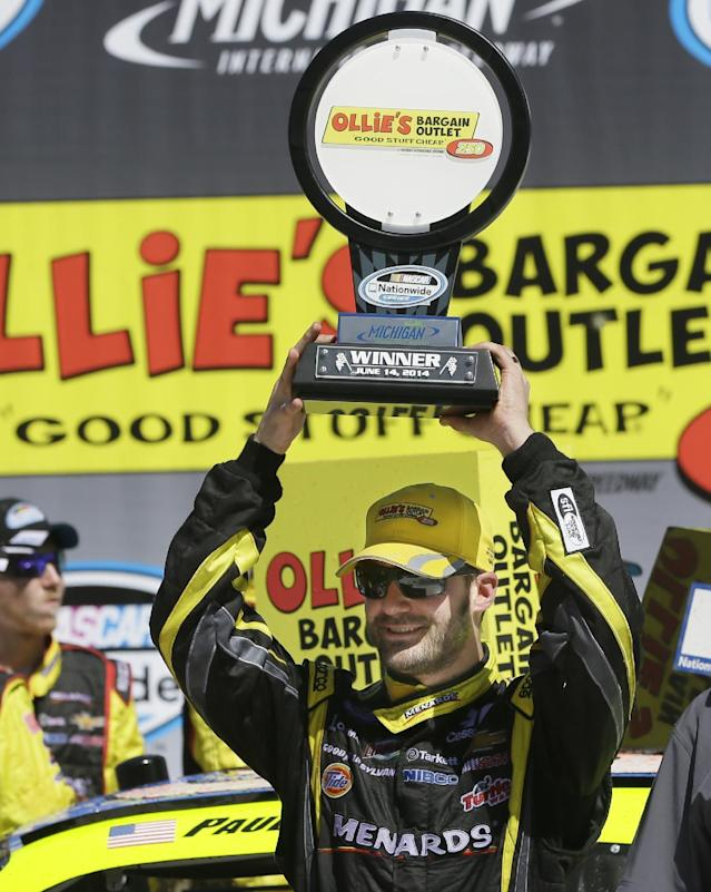 Driver Paul Menard holds up the trophy in Victory Lane after winning the NASCAR Nationwide Ollie's series auto race at Michigan International Speedway in Brooklyn, Mich., Saturday, June 14, 2014. (AP Photo/Carlos Osorio)