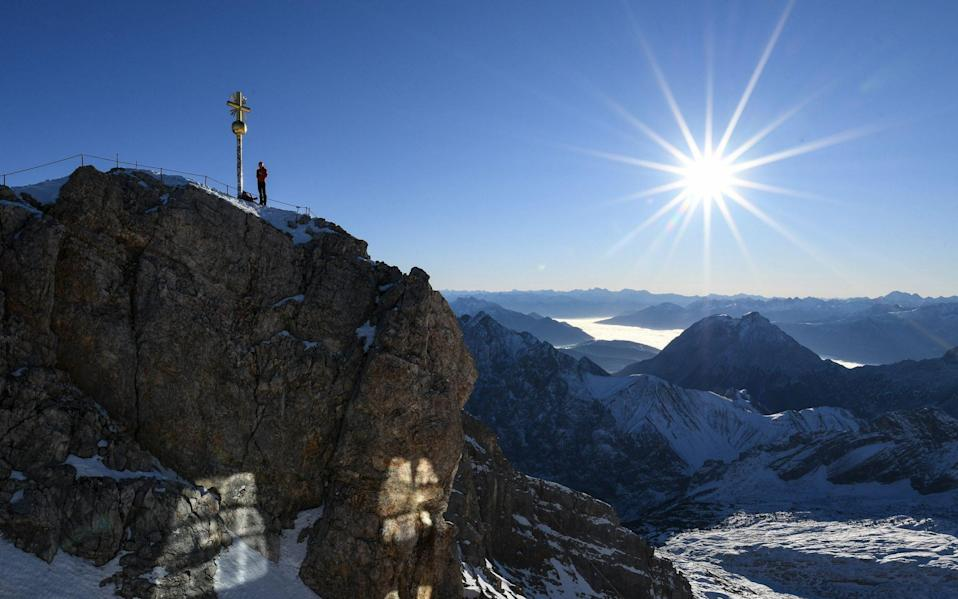 A mountaineer stands on the Zugspitze summit near Garmisch-Partenkirchen, Germany. Germany's highest ski resort, it is closed until at least December 20 - Shutterstock