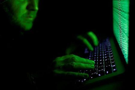 FILE PHOTO: A man types on a computer keyboard in front of the displayed cyber code in this illustration picture taken on March 1, 2017. REUTERS/Kacper Pempel/Illustration