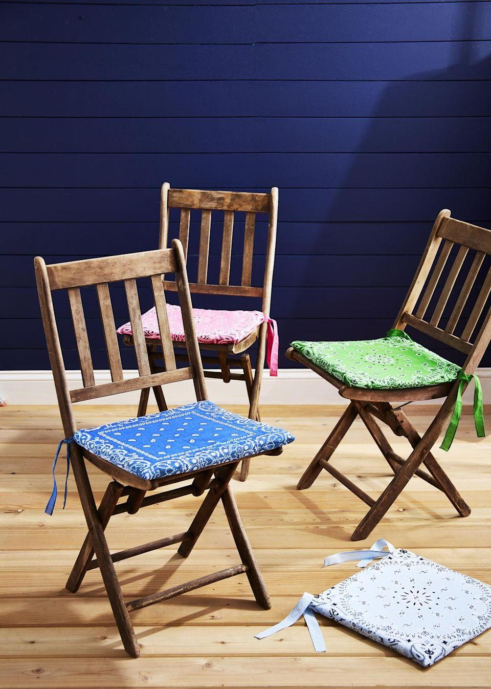 <p>Refresh your dining room or outdoor chairs by adding pops of color with these DIY bandana chair cushions.<strong><br></strong></p><p><strong>To make: </strong>Measure the seat of the chairs you wish to cover, and cut 1-inch-thick upholstery foam to size. Trim two bandanas to same size plus 1/2 inch all around to accommodate cushion's thickness. Sew bandanas together, leaving an opening large enough to slip foam through. Turn inside out, insert foam, and sew opening closed. Sew ribbon or strips of bandana to back corners for tying to chairs.<br></p>