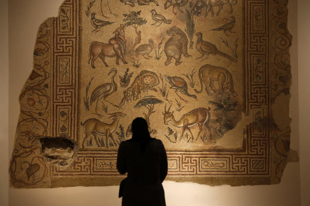 In this Jan. 28, 2016, photo, a visitor checks the mosaic of the Good Shepherd that was badly damaged in the lower left corner by a sniper during the 1975-1990 Lebanese civil war at the Lebanese National Museum in Beirut, Lebanon. Nearly 30 years after civil war guns fell silent, dozens of bullet-scarred, shell-pocked buildings are still standing _ testimony to a brutal conflict that raged for 15 years and took the lives of 150,000 people.(AP Photo/Hassan Ammar)