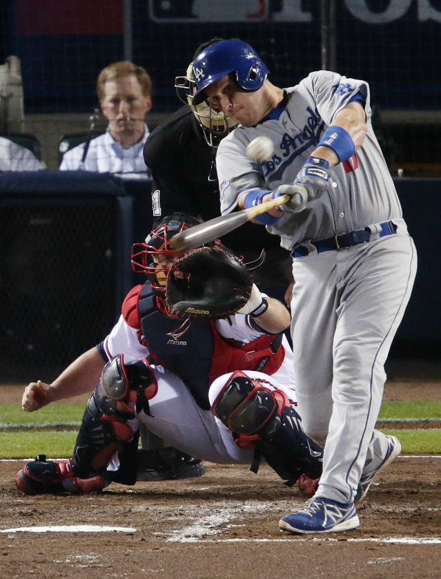 Los Angeles Dodgers' A.J. Ellis, right, hits a run-scoring double off Atlanta Braves starting pitcher Kris Medlen during the second inning of Game 1 of the National League Divisional Series, Thursday, Oct. 3, 2013, in Atlanta. (AP Photo/Dave Martin)